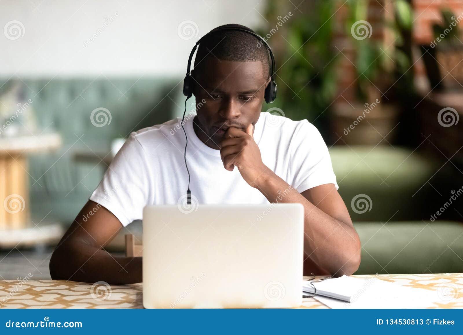 被聚焦的非裔美国人的男服耳机,使用膝上型计算机