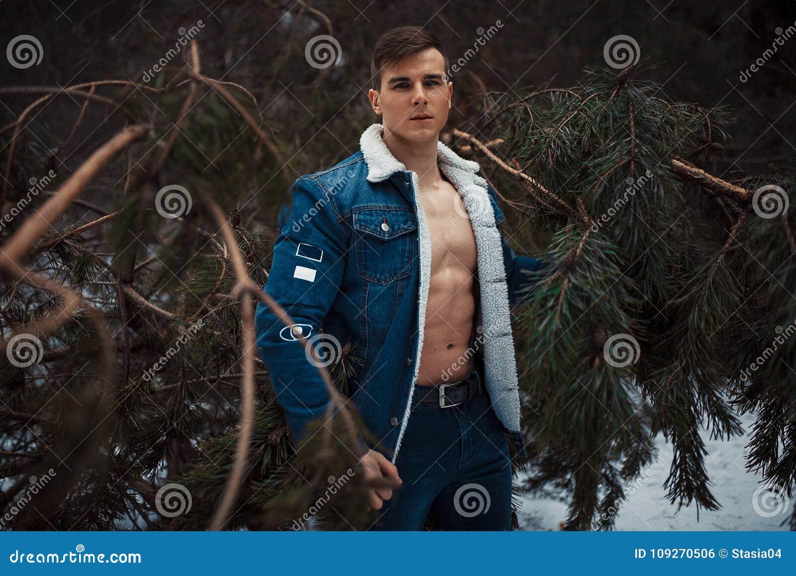 被解扣的夹克的年轻肌肉人有露出的乳房的在杉树旁边站立在冬天森林里