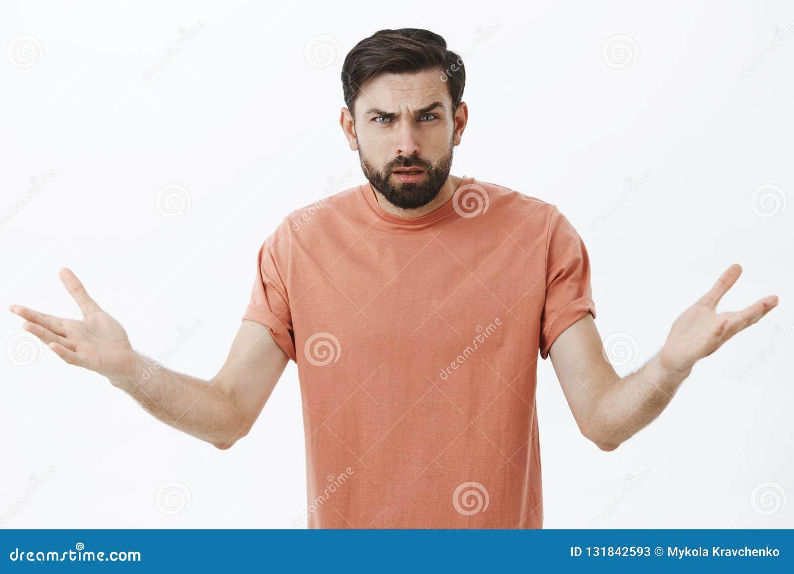 被迷惑的和懊恼恼怒的有胡子的男朋友为什么不可能知道争论,皱眉与无知情感耸肩