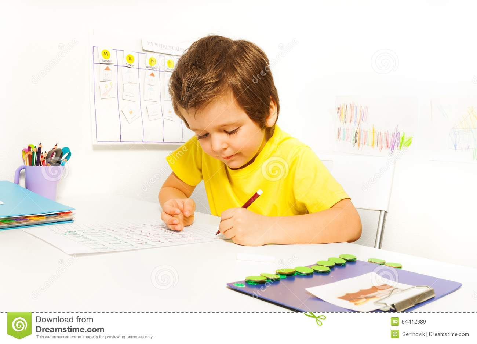 被集中的小男孩写与单独的铅笔