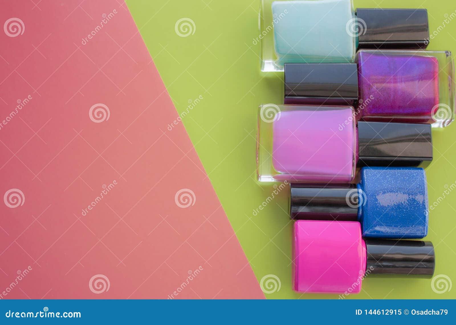 装瓶指甲油 一个小组在桃红色,绿色背景的明亮的修指甲 在左边的空的空间