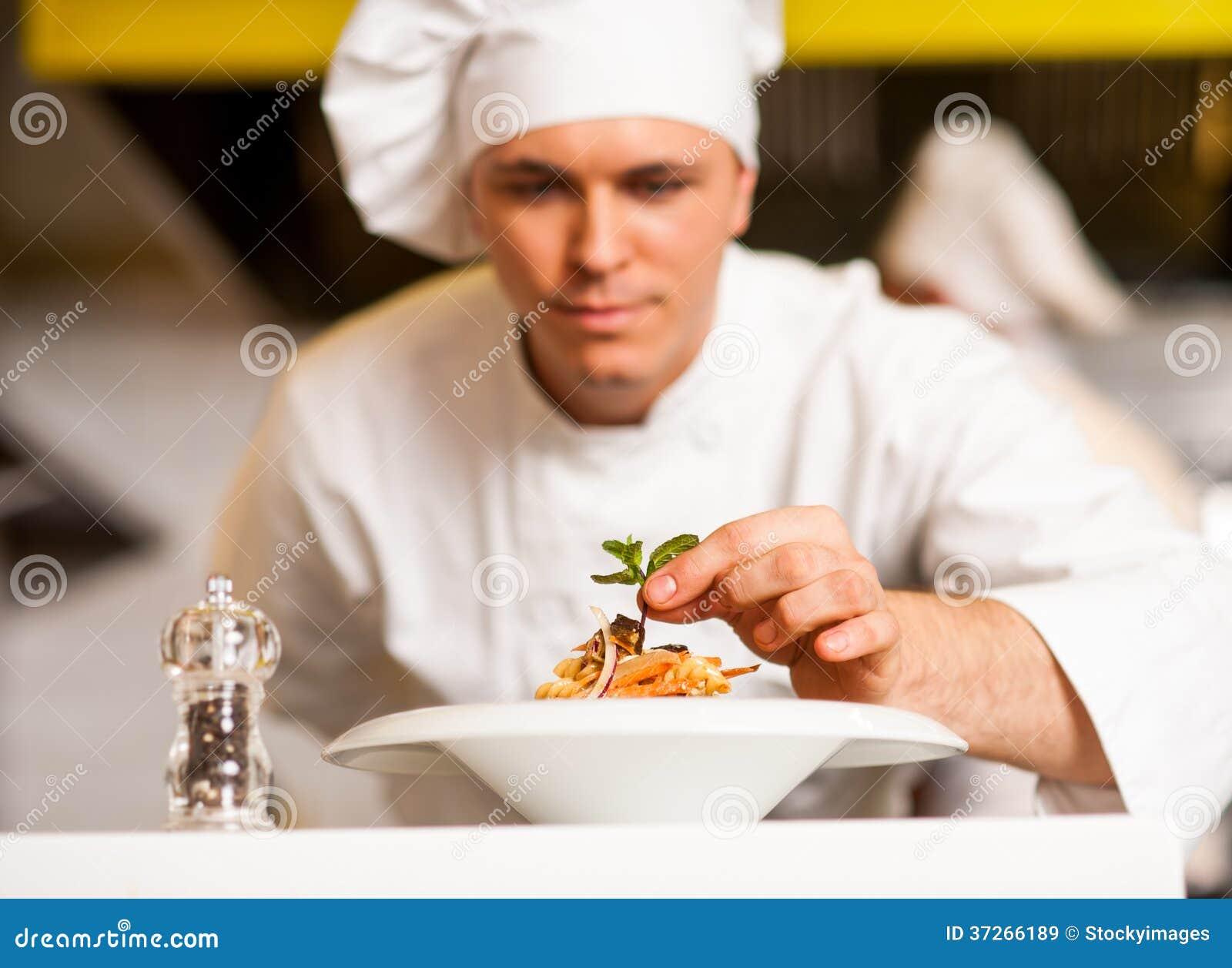 装饰与草本叶子的厨师意大利面制色拉