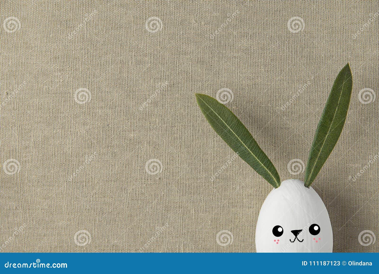 装饰白色与拉长的逗人喜爱的Kawaii微笑的面孔的被绘的复活节彩蛋兔宝宝 绿色留下耳朵 米黄亚麻制织品背景