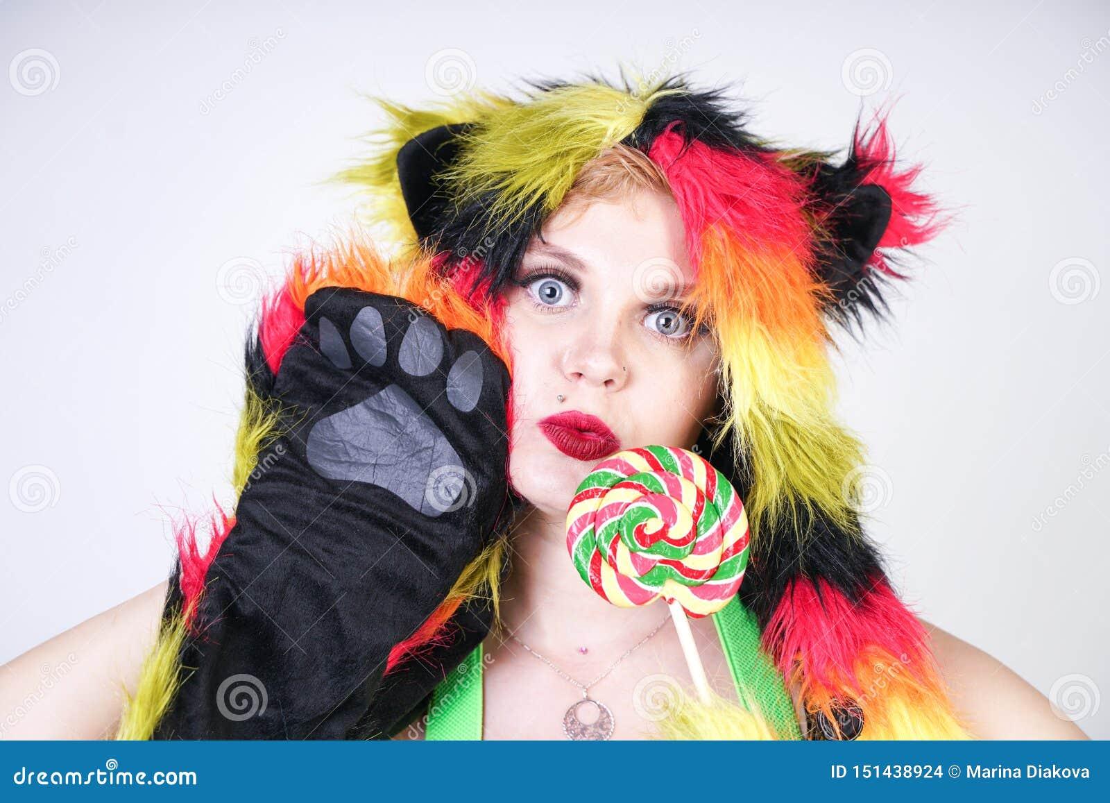 裘皮帽的迷人的正大小年轻女人由与摆在绿色悬挂装置,黑胸罩的猫耳朵和爪子的多彩多姿的纤维做成