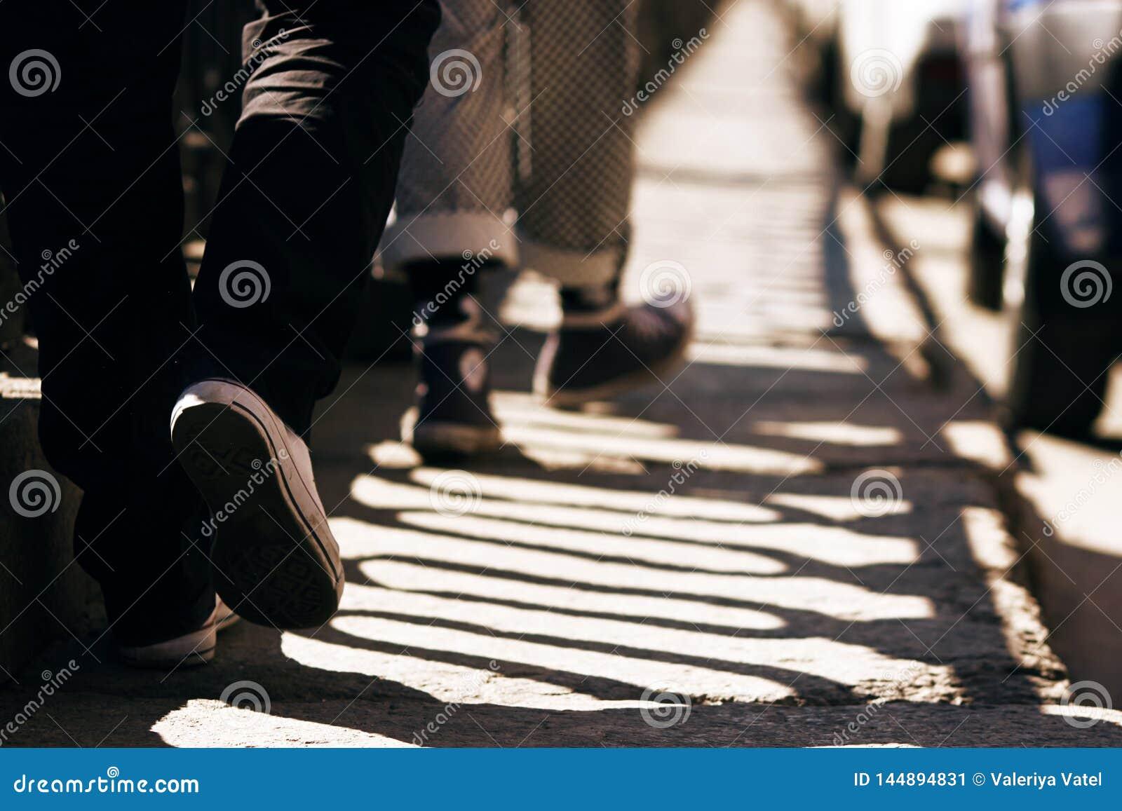 裤子和运动鞋的两个人走在石路面的