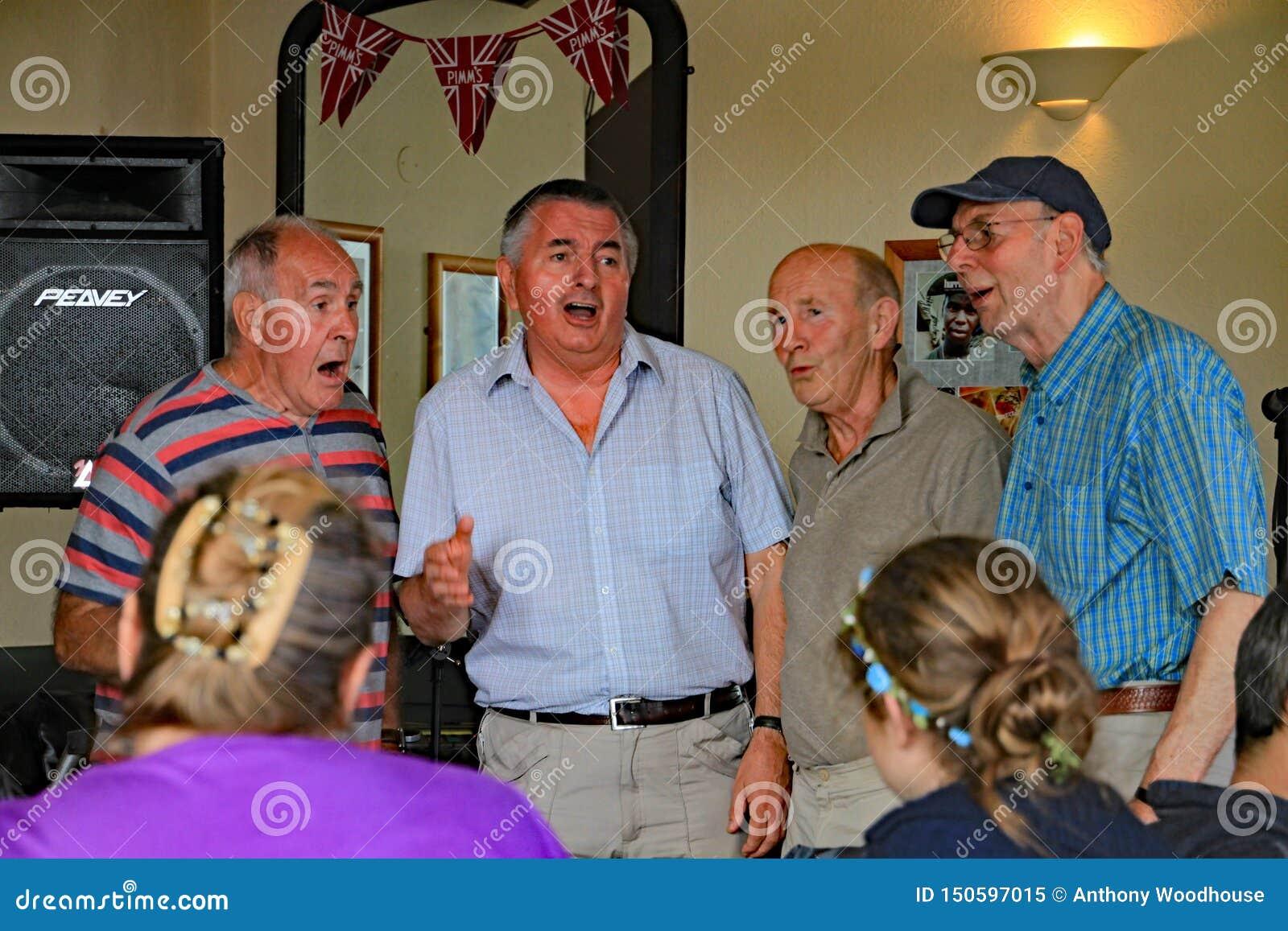 西德茅斯,德文郡,英国- 2012年8月5日:四位更加成熟的歌手执行acapella在一个开放话筒会议在海滨人行道客栈