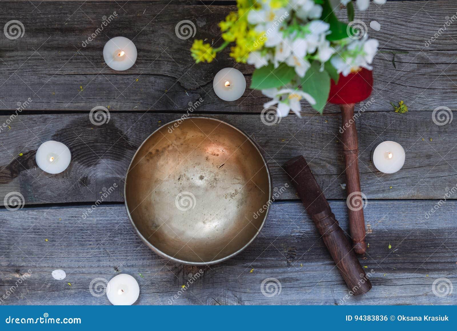 西藏唱歌碗和特别棍子、灼烧的蜡烛和花瓶有花的在黑暗的木背景,顶视图 有选择性