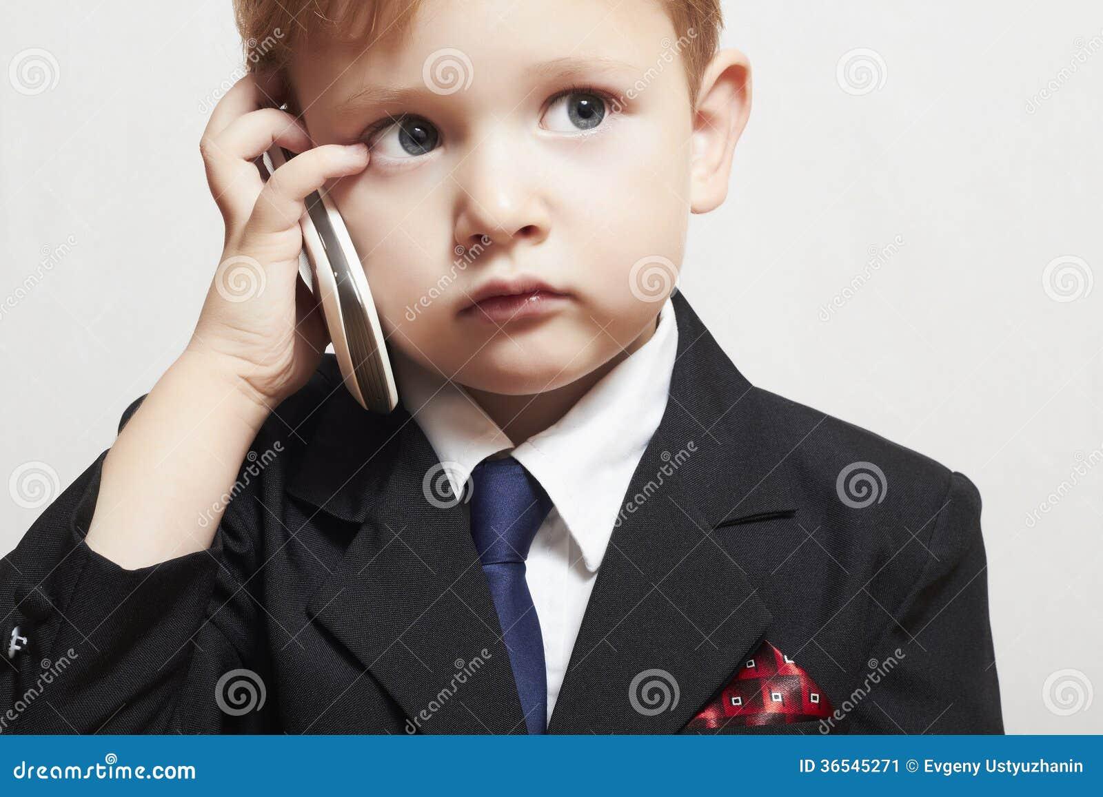 西装的小男孩有手机的。英俊的孩子。时兴的孩子