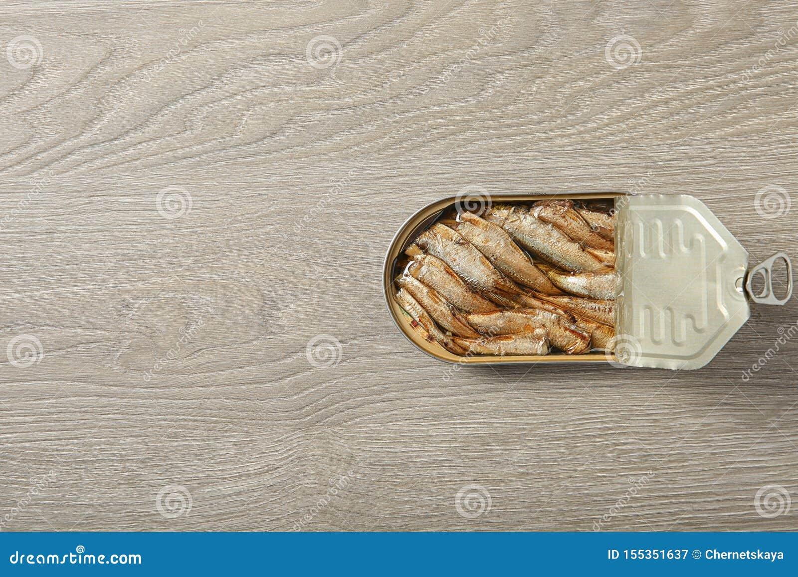 西鲱开放锡罐在木背景,顶视图的