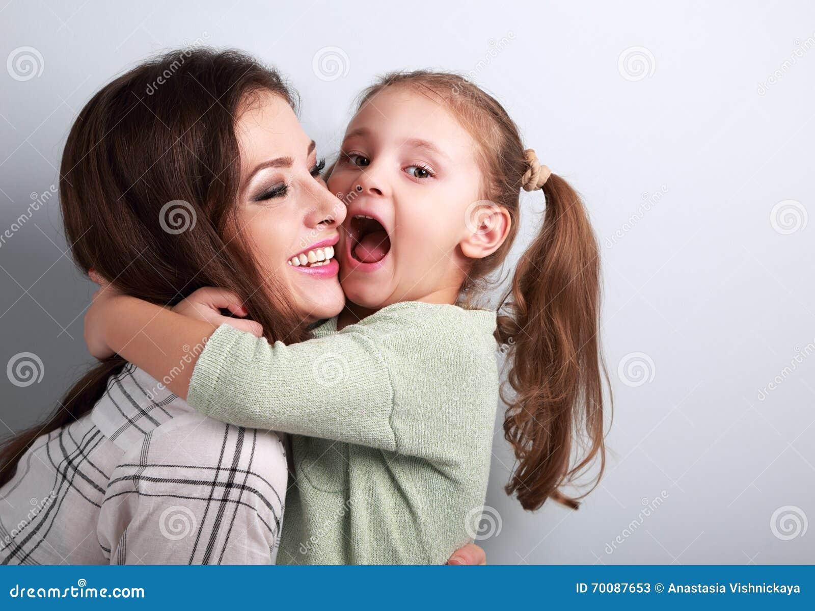 要对咬住的愉快的做鬼脸的孩子她没有的笑的母亲