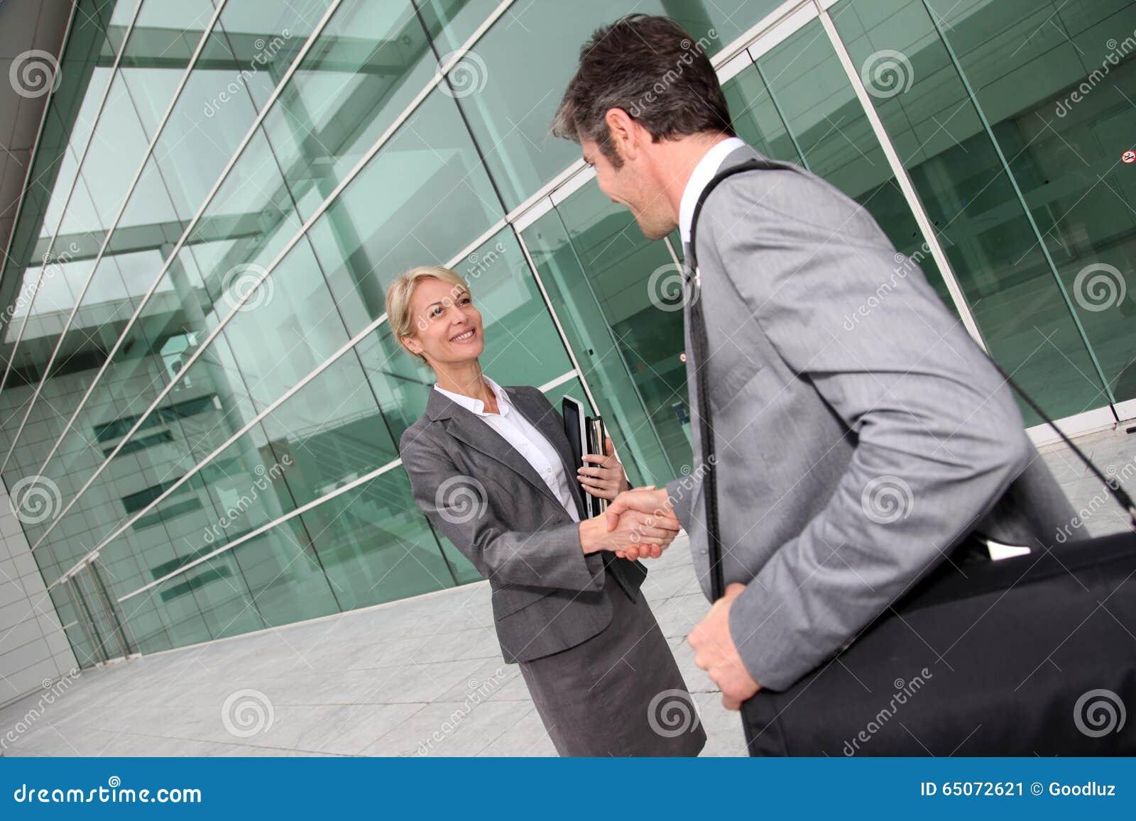 见面在办公楼前面的商人