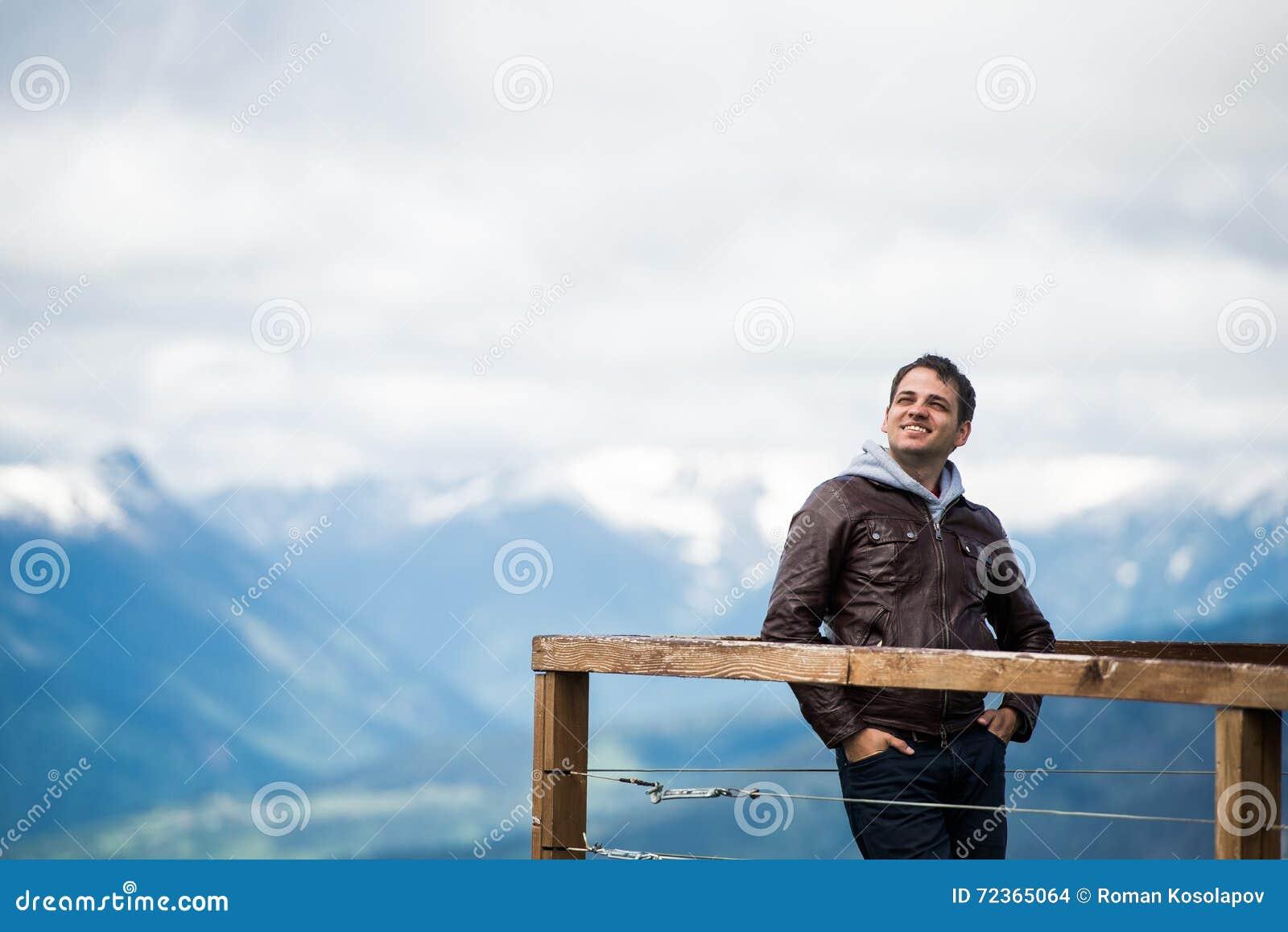 观点的人在山 愉快和微笑,看对天空