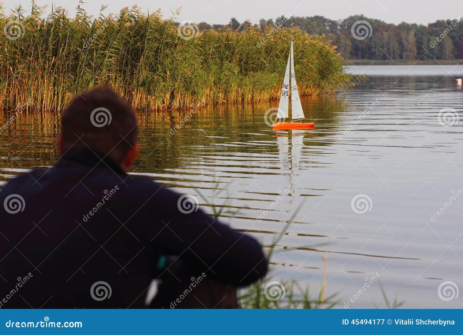 观看一条无线电操纵的小船的人