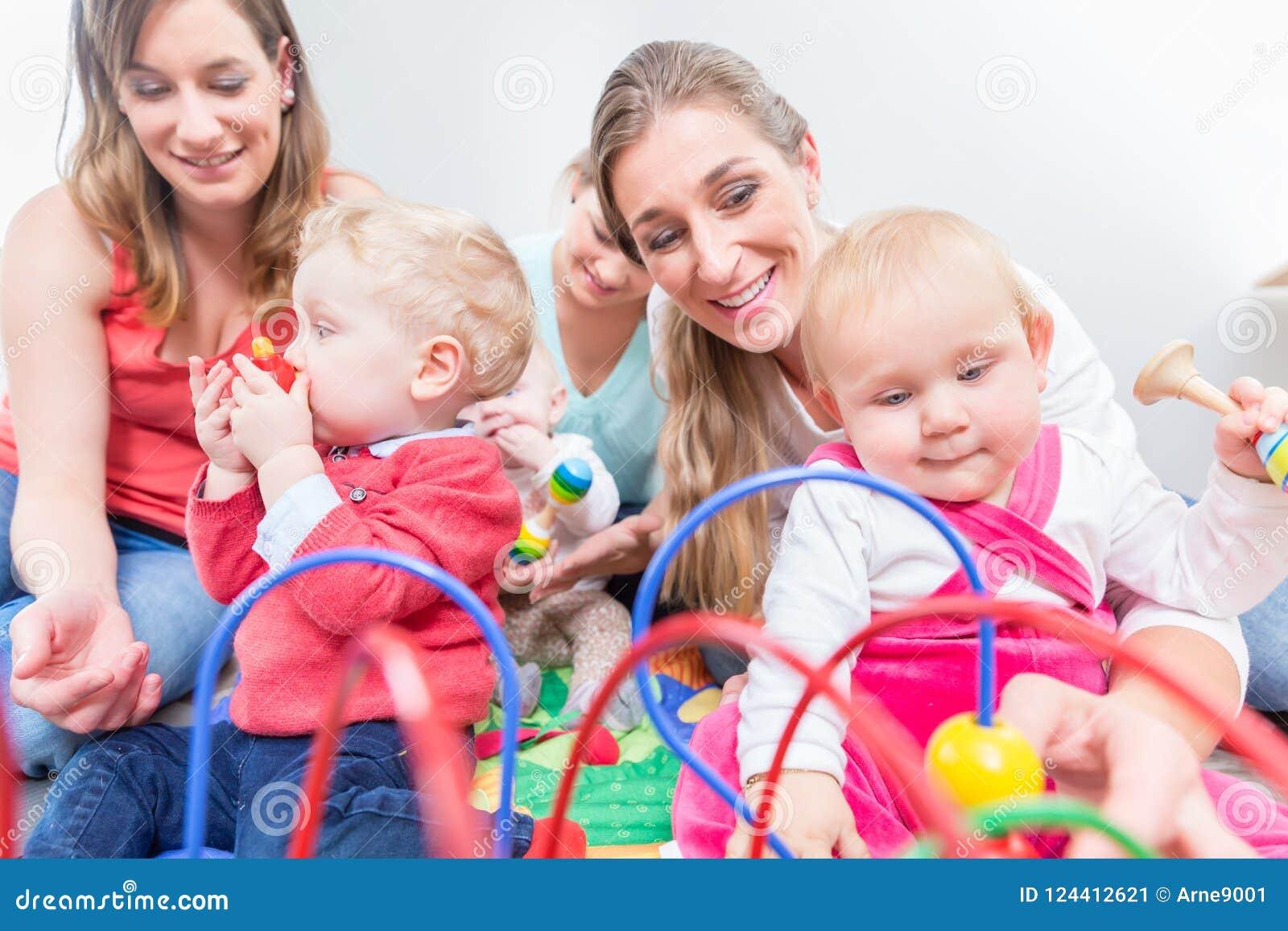 观看他们逗人喜爱和健康婴孩的小组愉快的年轻母亲使用