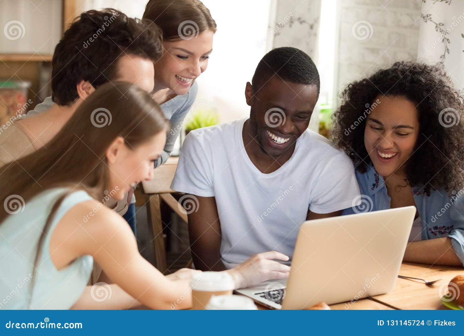观看喜剧电影的不同的学生坐在书桌在屋子里