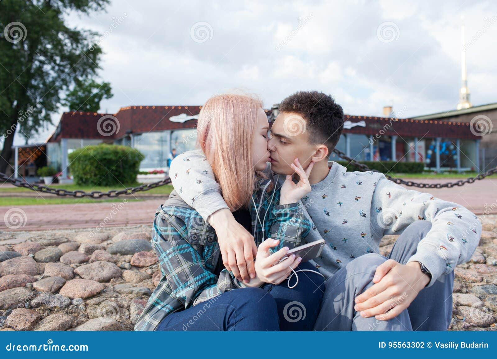 观看在一个智能手机的年轻夫妇录影在海滩河 他们微笑,看滑稽的录影