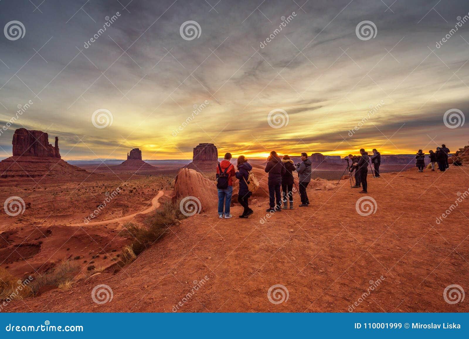 观看在纪念碑谷的游人日出