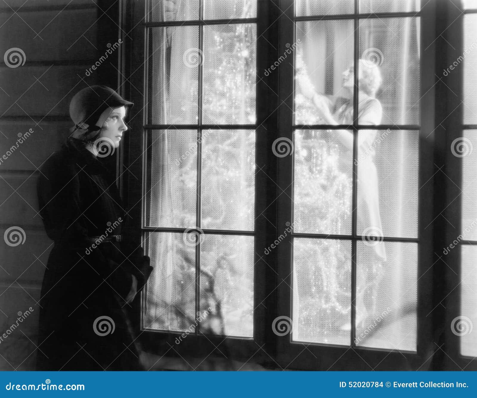 观看妇女的窗口的妇女常设外部整理圣诞树(所有人被描述不是更长生存和不