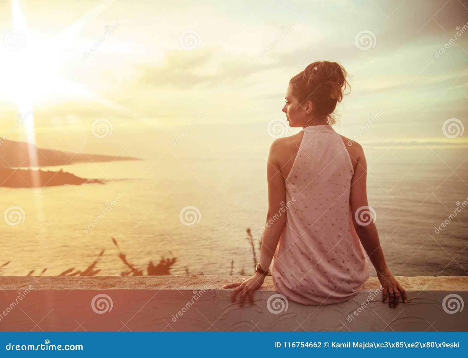 观看美好的日落的深色的镇静夫人
