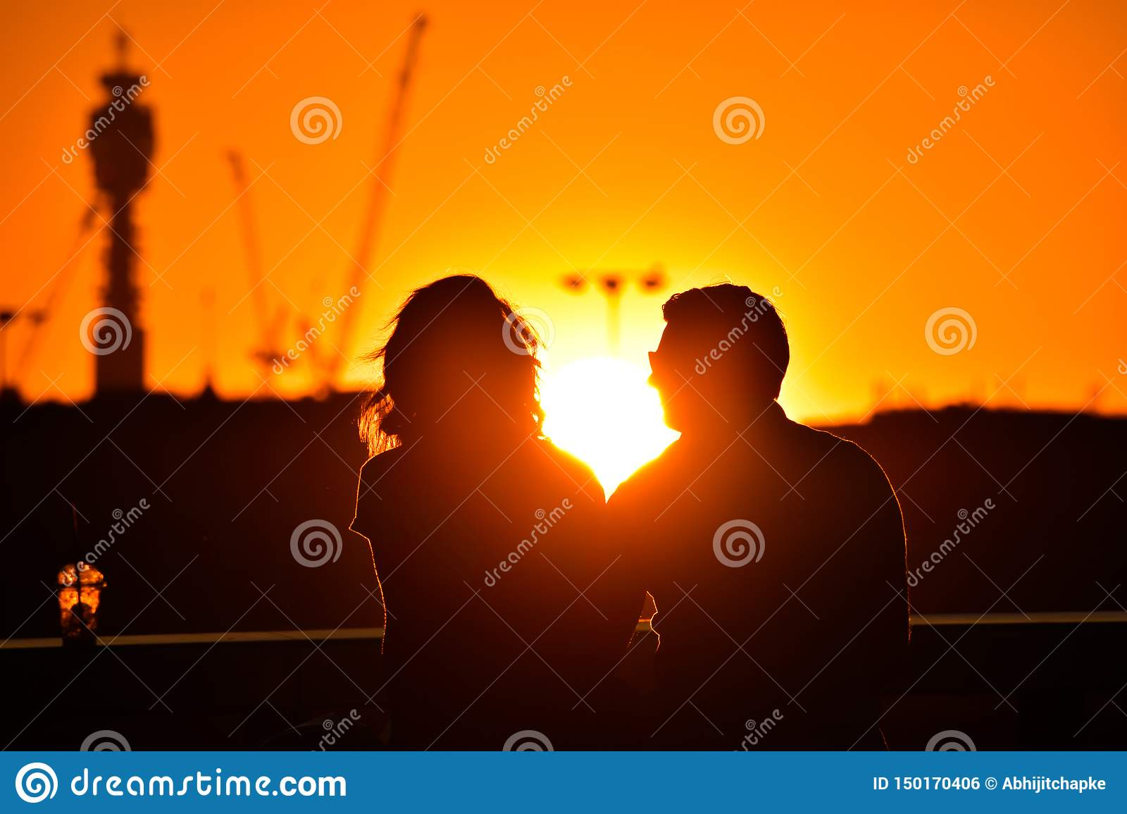 观看美好的明亮的浪漫日落的爱的夫妇剪影