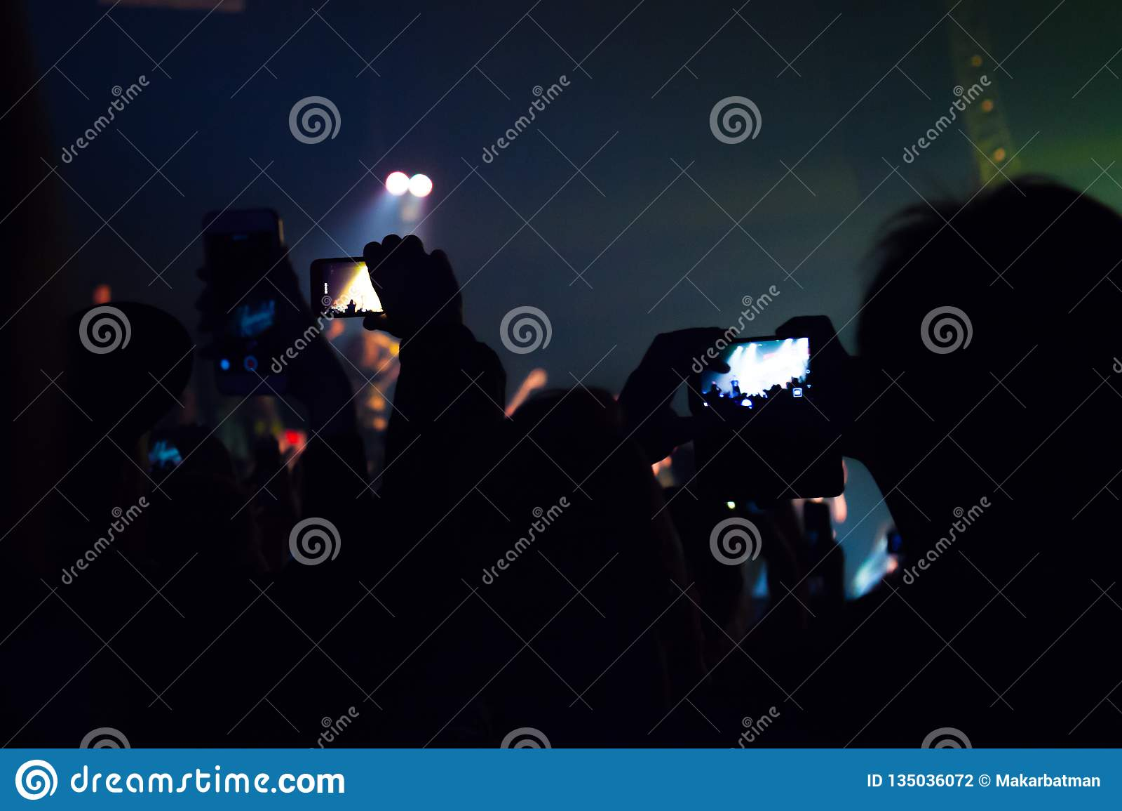 观看音乐会和某人的人们射击照片和录影有手机的