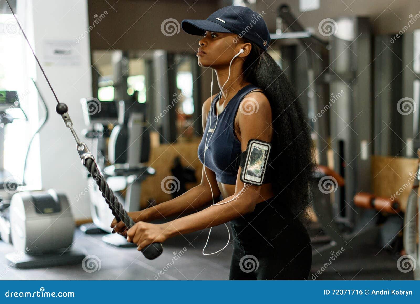 解决在健身房的性感的华美的非裔美国人的妇女侧视图和听到在白色耳机的音乐