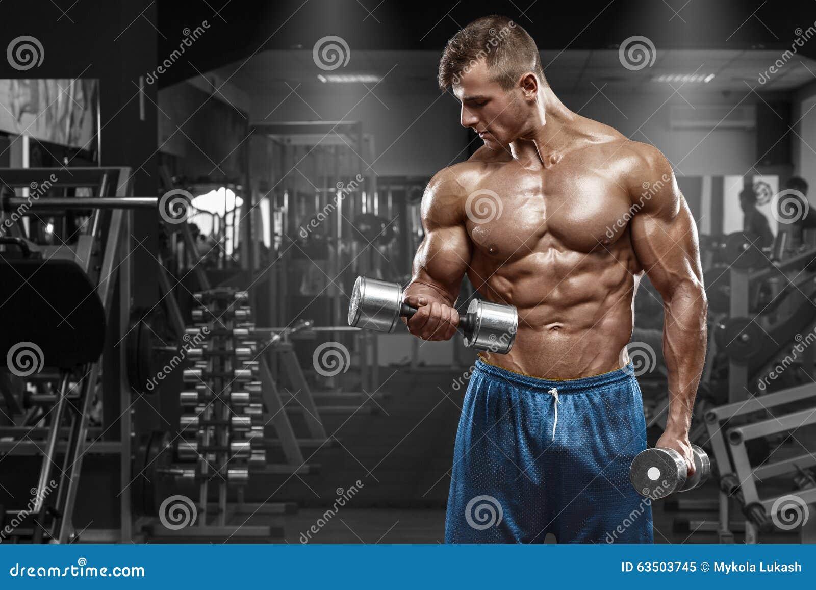 解决在健身房的肌肉人做与哑铃的锻炼在二头肌,强的男性赤裸躯干吸收
