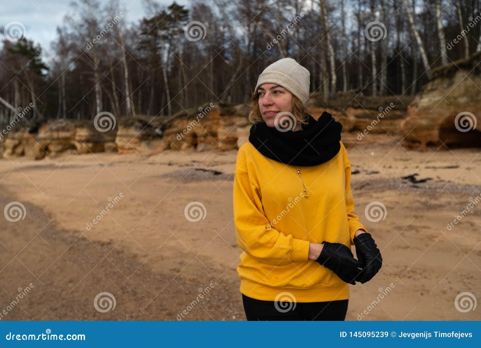 解决在海滩的愉快的体育和时尚恋人热心者穿明亮的黄色毛线衣和黑手套和盖帽