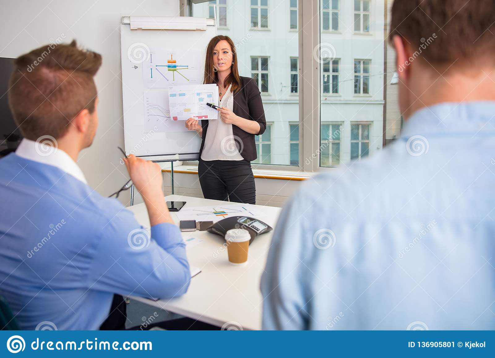 解释图的女实业家对同事在办公室