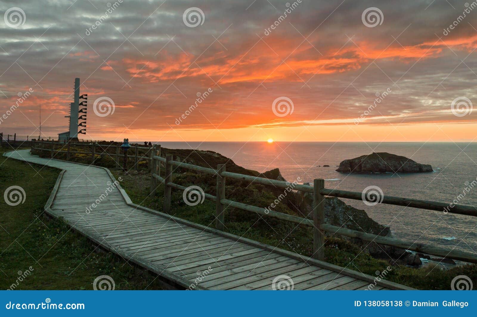 警告号角和木走道在灯塔Peñas海角附近在阿斯图里亚斯,西班牙的美丽的日落海岸
