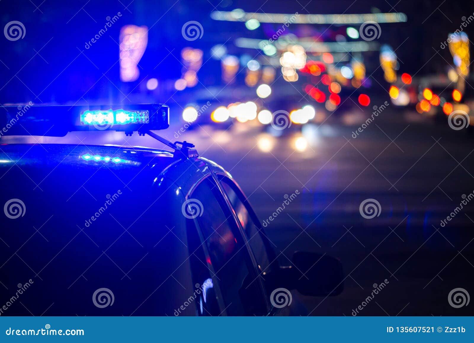 警车光在晚上在有选择聚焦和bokeh的城市