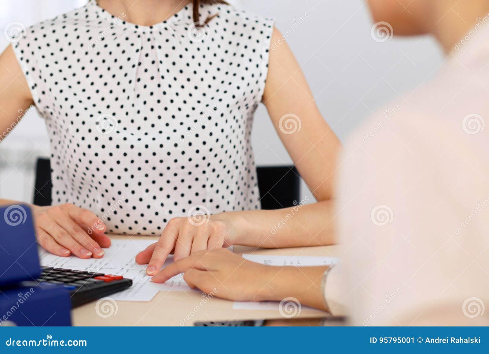 计数在报税表完成的计算器收入的两名女性会计递特写镜头 国税局