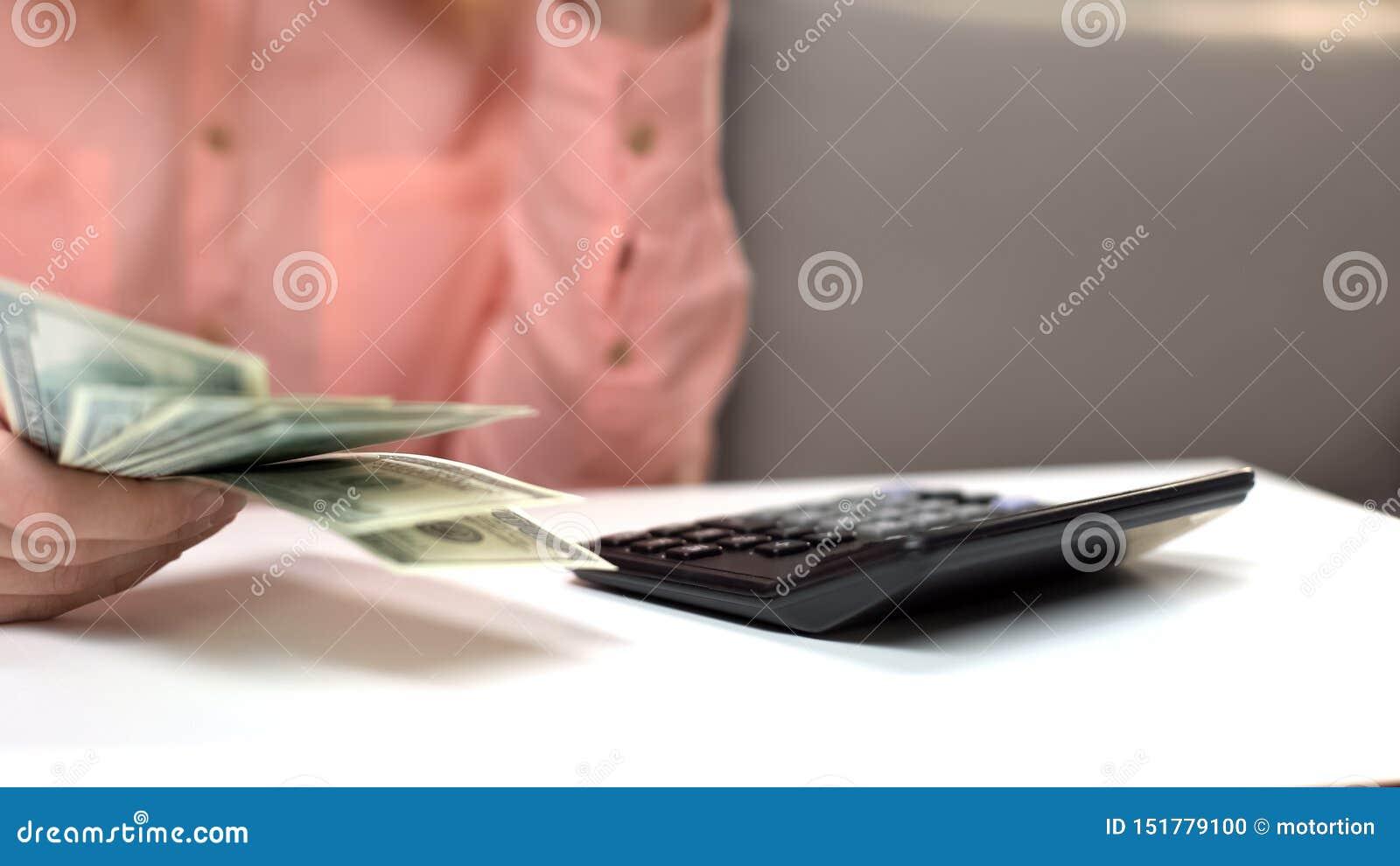 计数税,在桌,金融投资上的计算器的在手中妇女美元