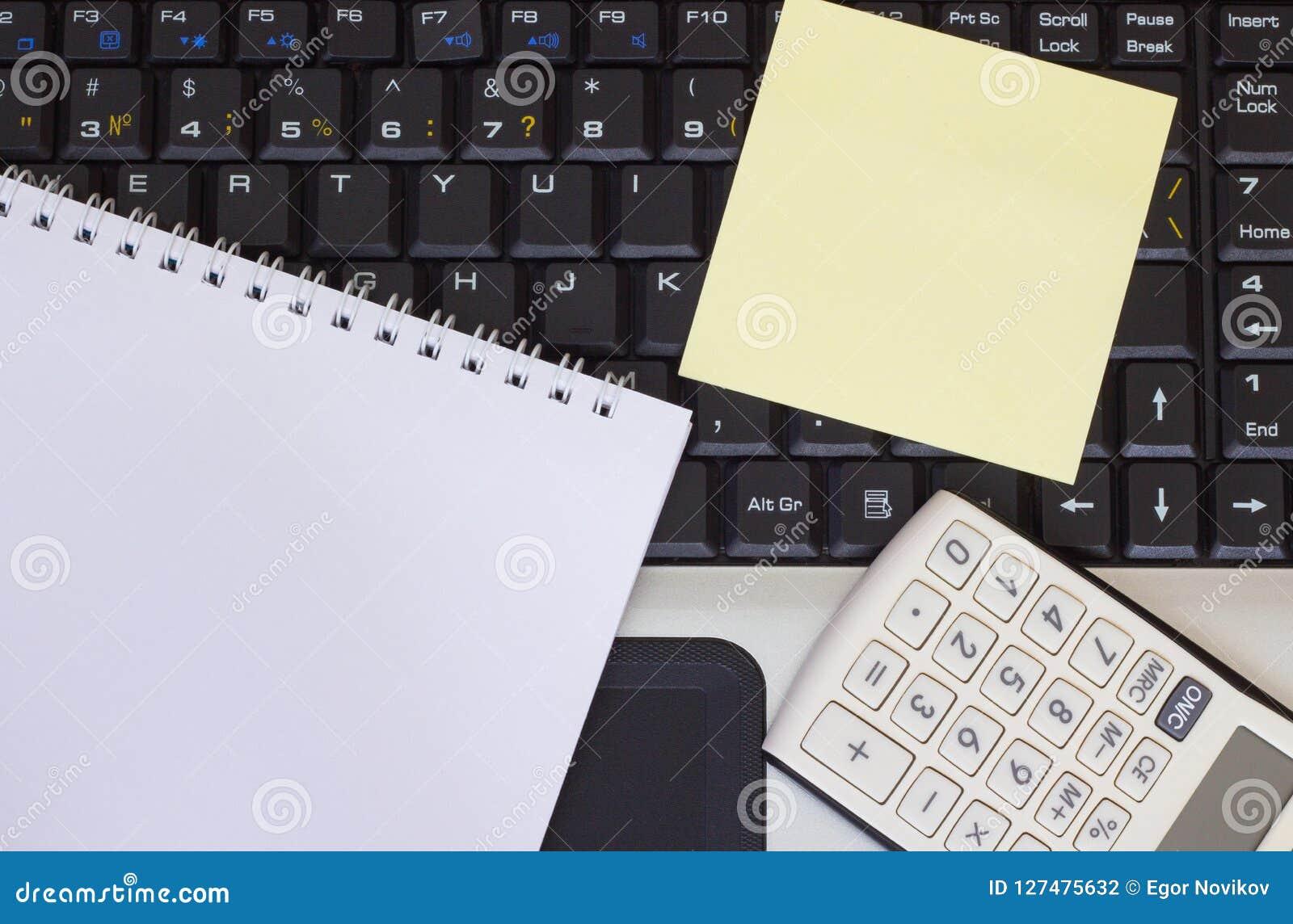 计算器、智能手机和片剂在膝上型计算机键盘,特写镜头