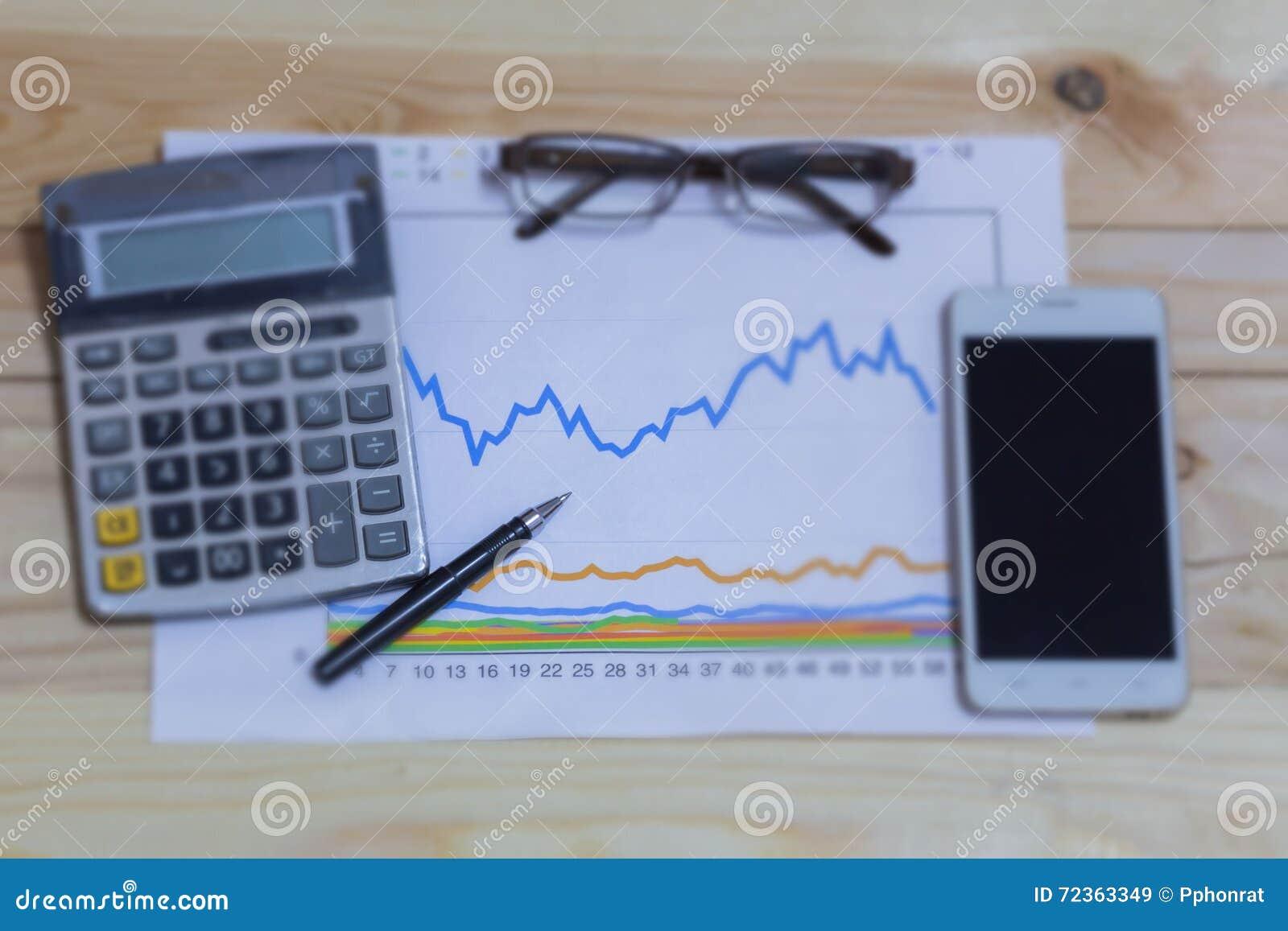 计算器、电话、笔和玻璃在财政图表,事务c