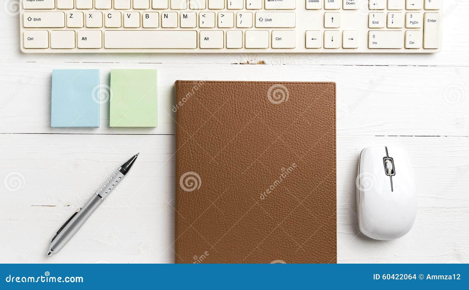 计算机和棕色笔记本有办公用品的