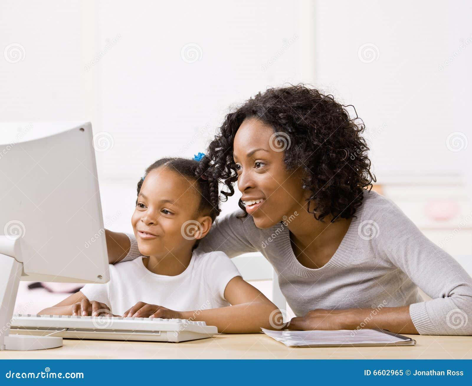 计算机执行女孩帮助的家庭作业母亲
