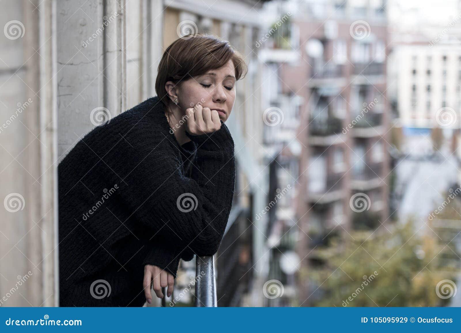 认为和感觉哀伤的遭受的消沉的年轻美丽的妇女在都市城市背景家阳台