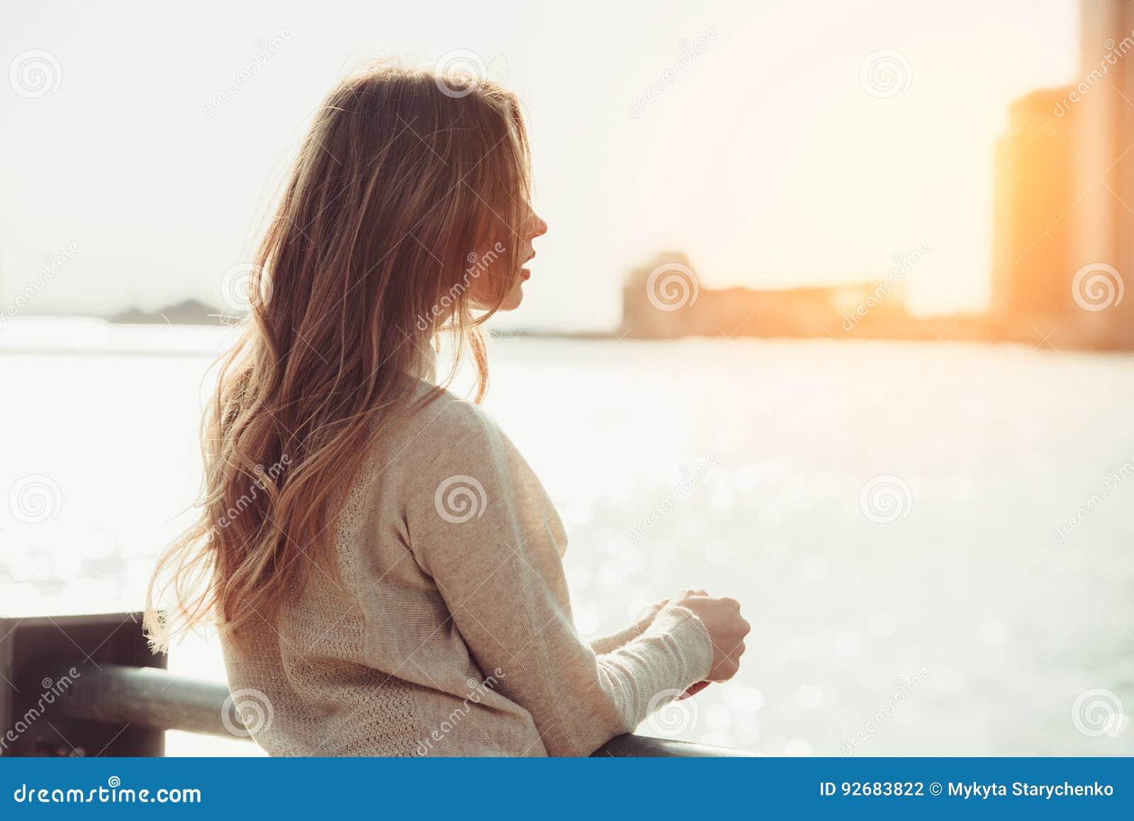 认为美丽的孤独的女孩作梦和,当等待在城市海洋码头的日期在日落时间时