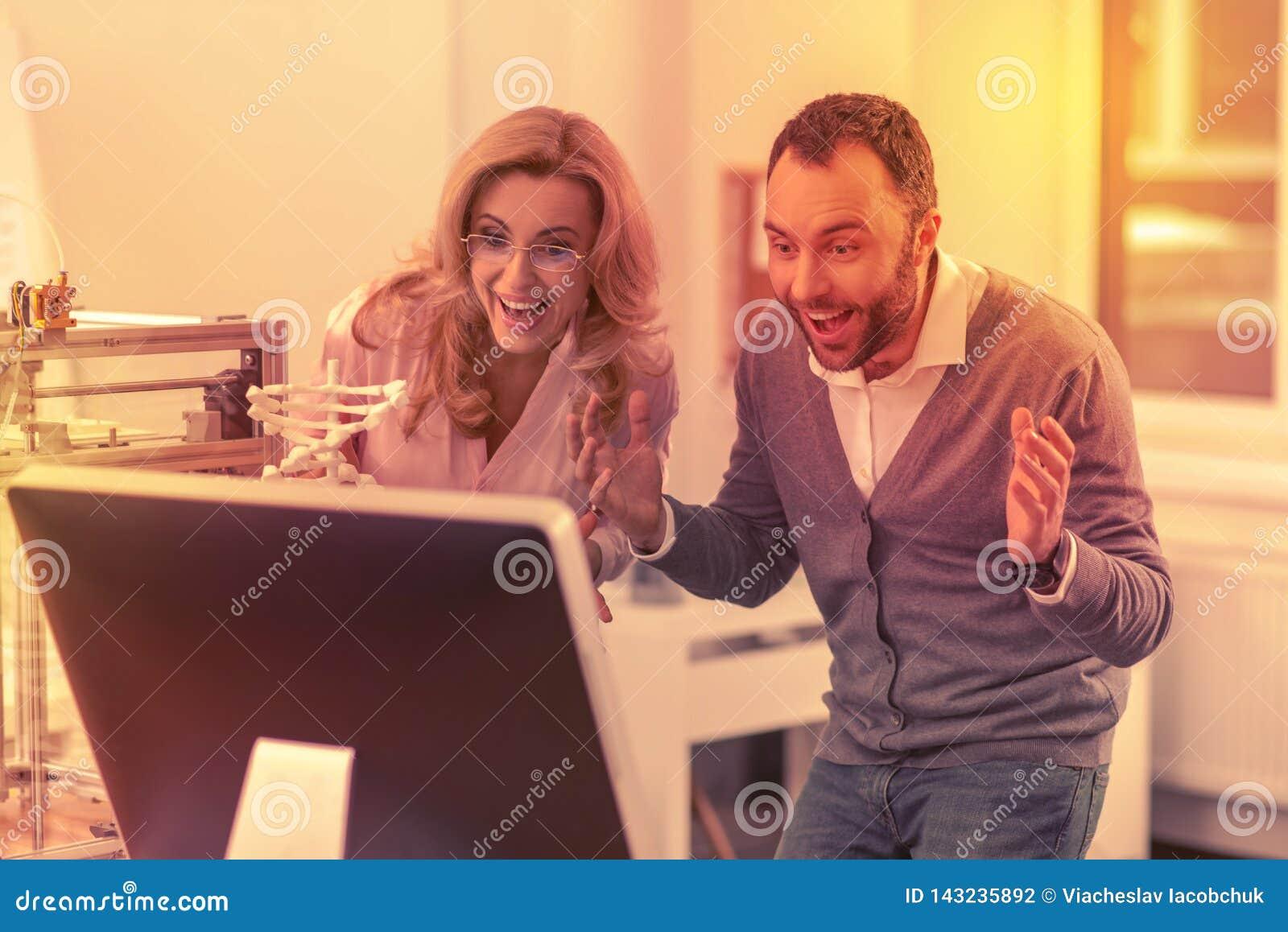 认真男人和妇女兴奋看他们的工作的巨大结果