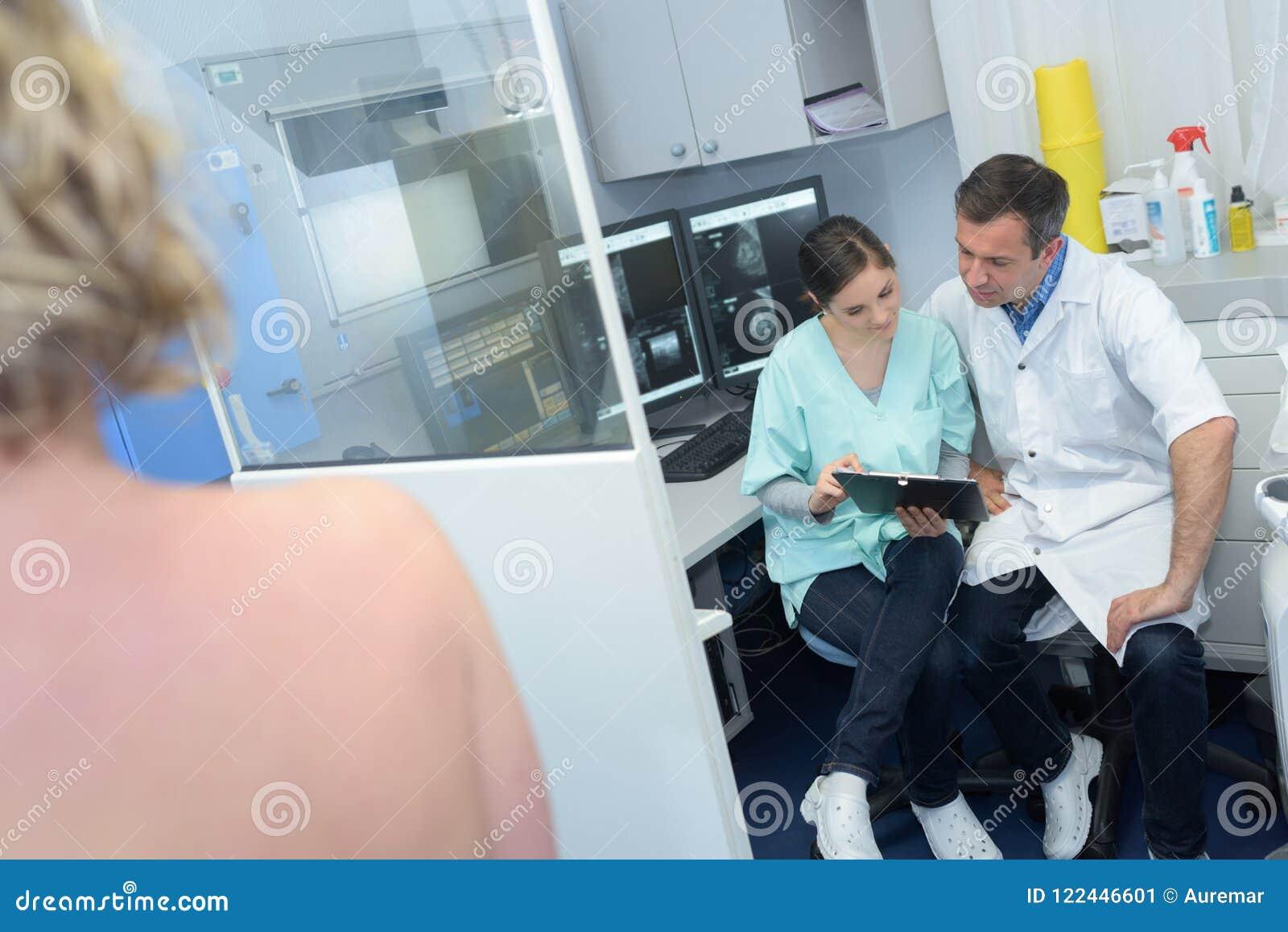 讨论患者赤裸肩膀的放射学医护人员在前景