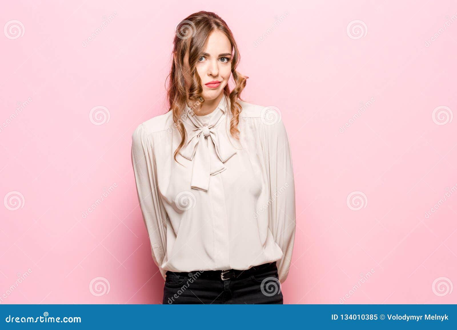 让我认为 有做出选择的周道的表示的半信半疑的沉思妇女反对桃红色背景