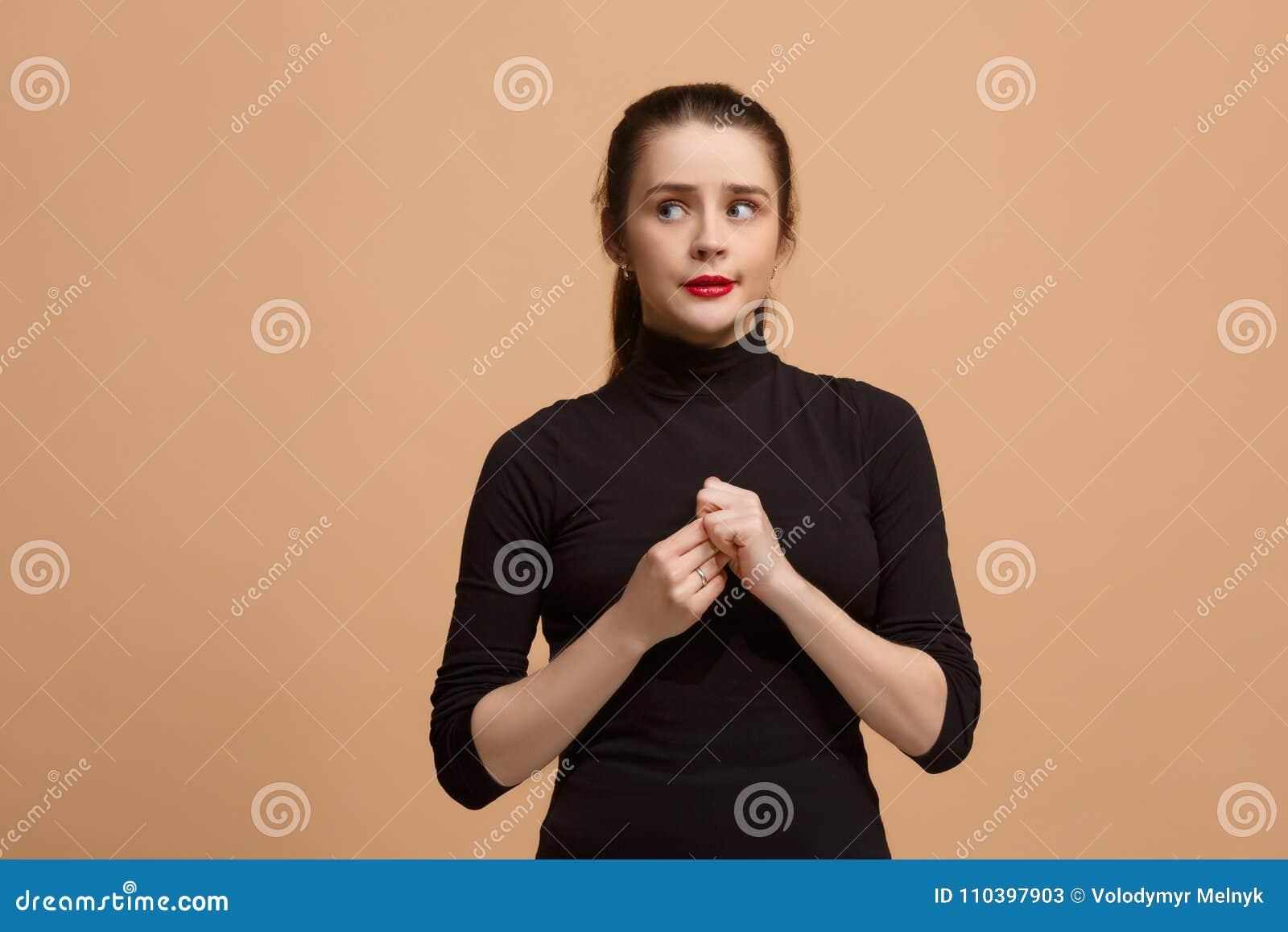 让我认为 有做出选择的周道的表示的半信半疑的沉思妇女反对淡色背景