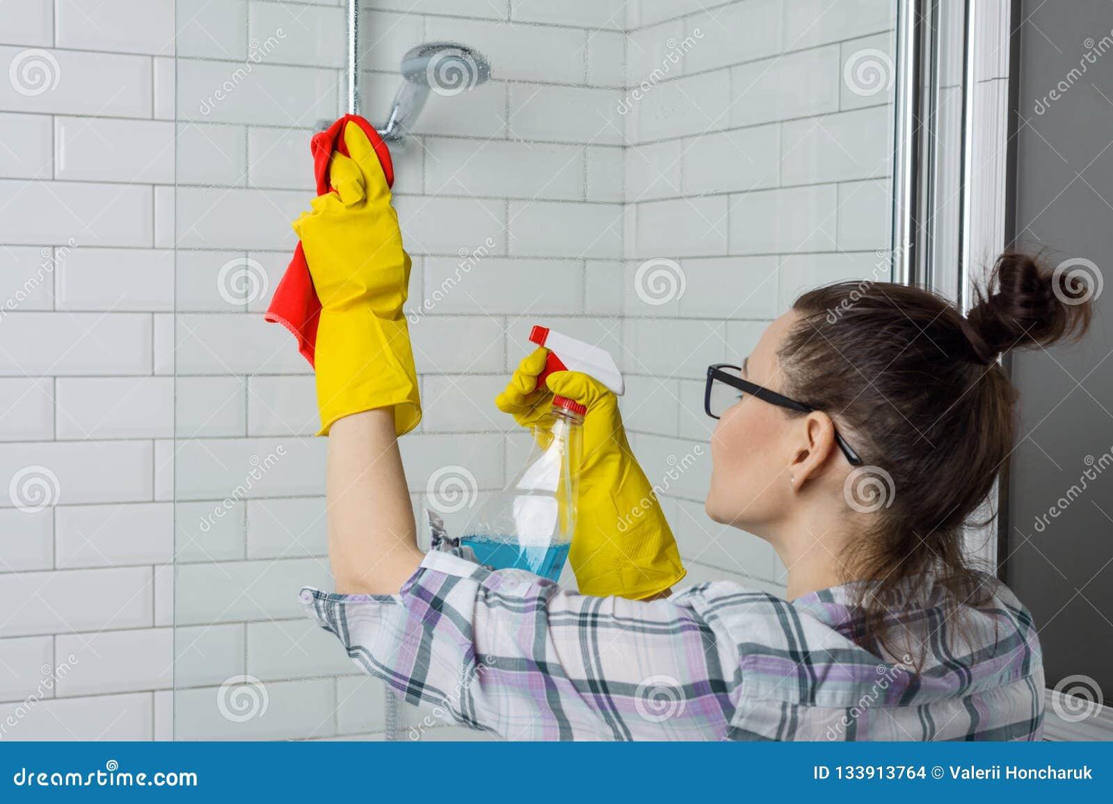 议院清洁 在家清洗卫生间的妇女,女性在便服与洗涤剂和洗碗布在卫生间里