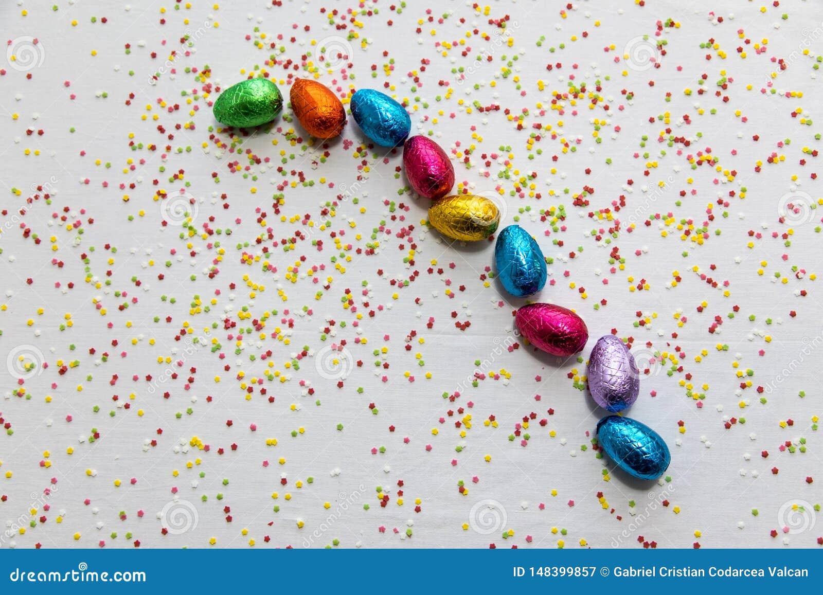 许多排列了在白色背景和五颜六色的五彩纸屑的色的巧克力复活节彩蛋