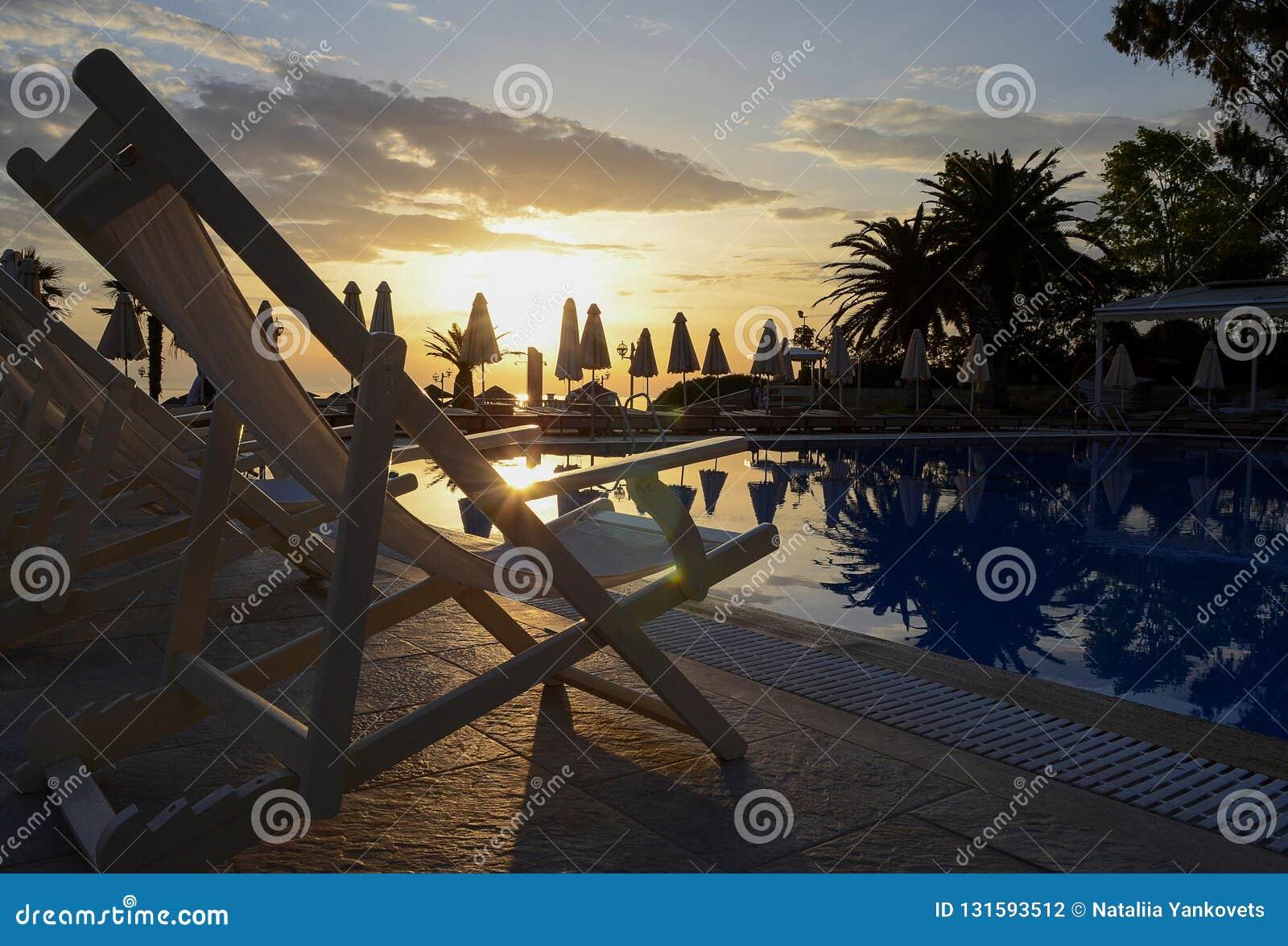 许多白色躺椅在游泳场附近站立反对黎明天空和沙滩伞的背景