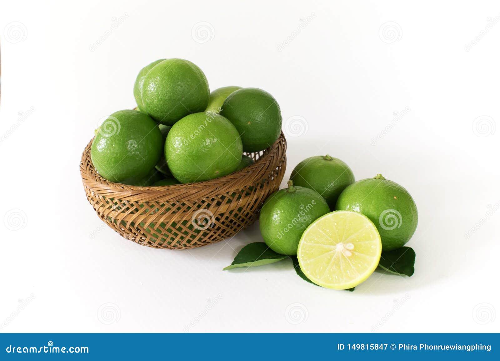 许多绿色柠檬在一个木篮子 并且某些与柠檬切片的外部在边切成了两半