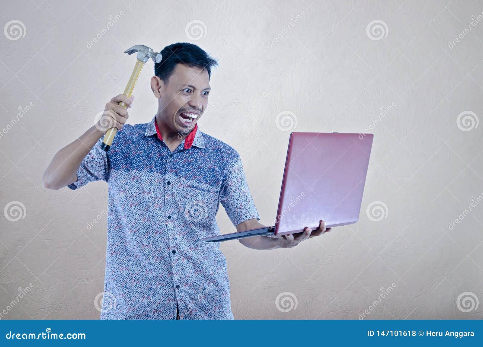 设法亚裔的年轻人由发嗡嗡声的东西打破膝上型计算机
