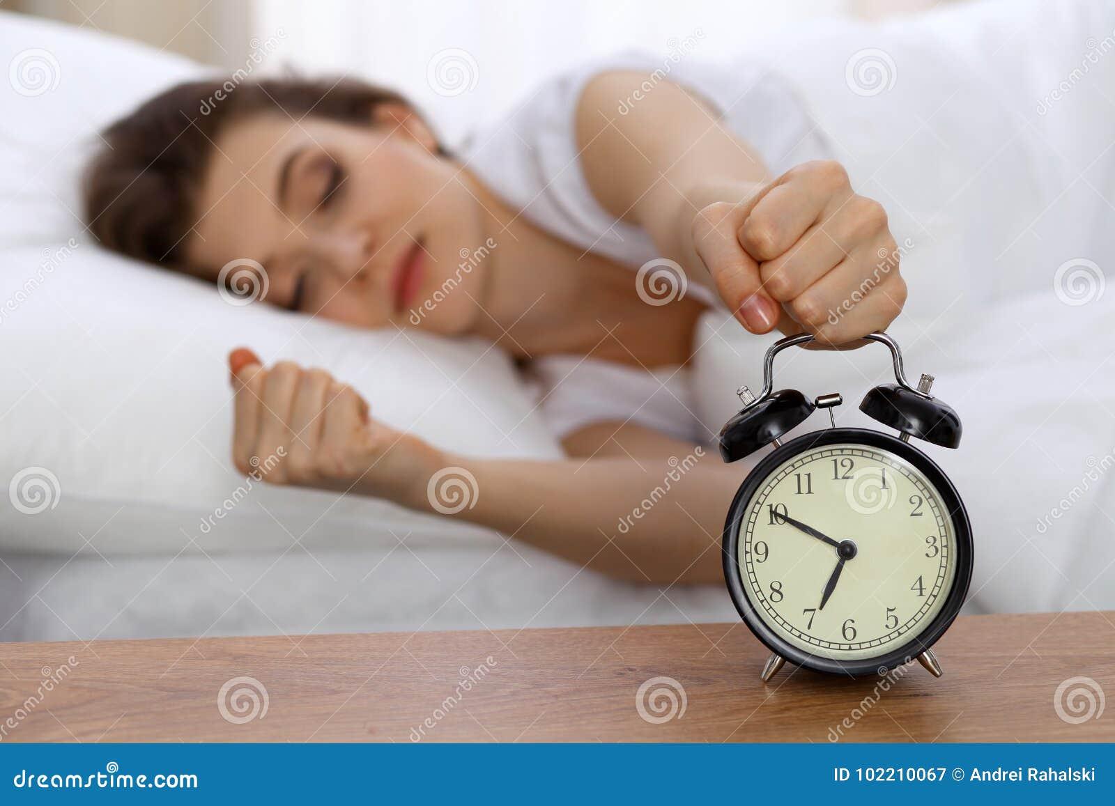 设法美丽的睡觉的妇女休息在床上和醒与闹钟