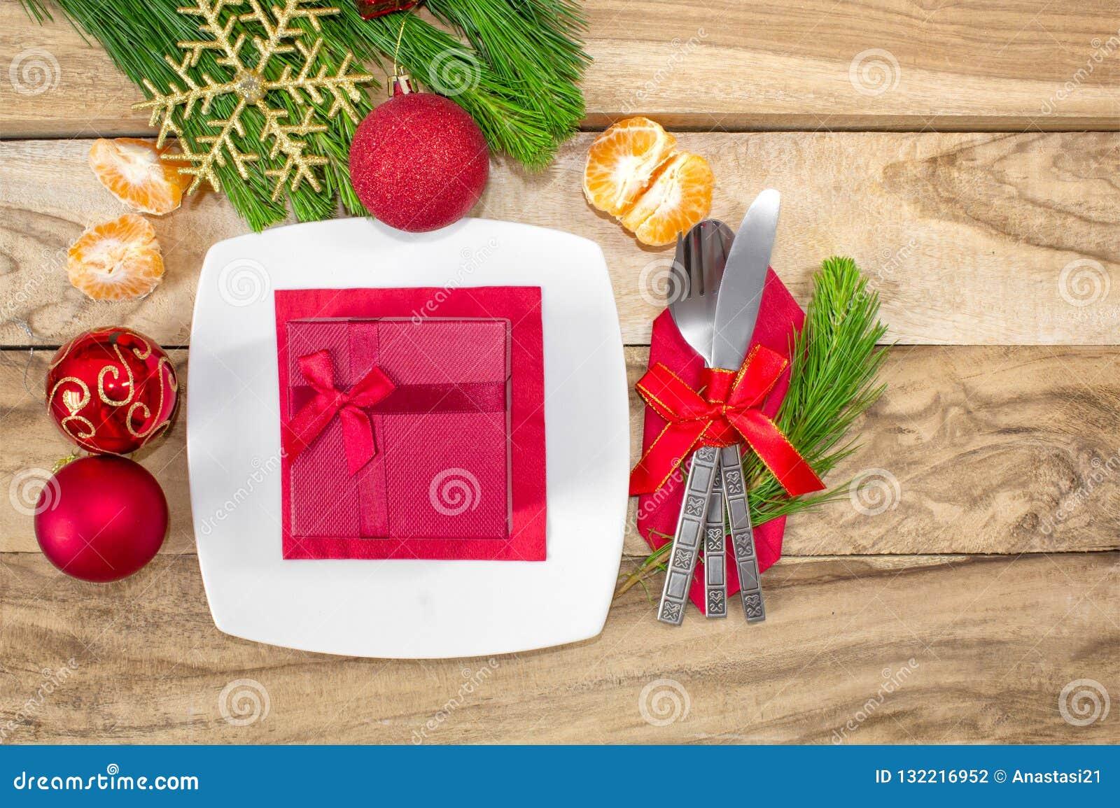 设置为圣诞节桌、蜜桔、装饰、冷杉和一块板材有礼物和利器的 欢乐的背景 背景上色节假日红色黄色